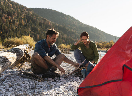 Mature couple camping at riverside with wood for a camp fire - UUF16269