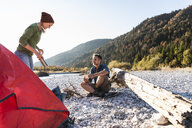 Mature couple camping at riverside in the evening light - UUF16272