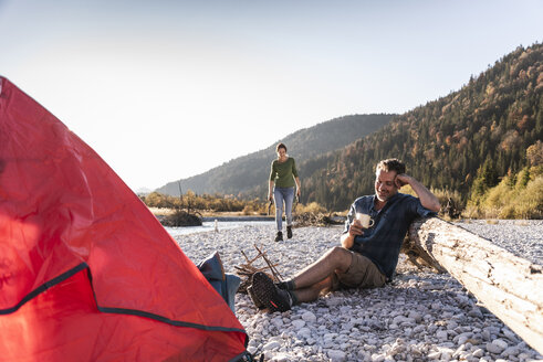 Mature couple camping at riverside in the evening light - UUF16275