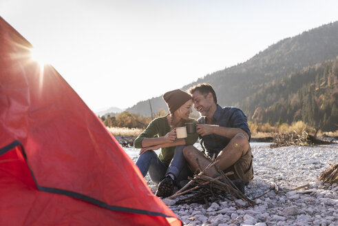 Mature couple camping at riverside in the evening light - UUF16278