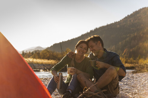 Mature couple camping at riverside in the evening light - UUF16281