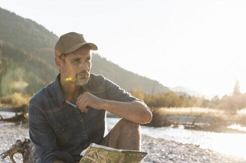 Mature man camping at riverside - UUF16290