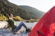 Mature woman camping at riverside in the evening light - UUF16299