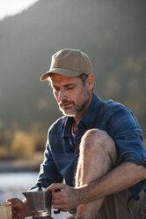 Mature man camping at riverside, using espresso machine - UUF16305