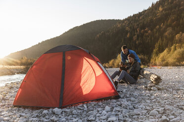Mature couple camping at riverside in the evening light - UUF16311