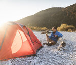 Mature man camping at riverside, using tablet - UUF16314