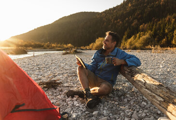 Mature man camping at riverside, holding tablet and cup - UUF16317