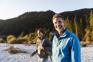 Mature couple hiking at riverside in the evening light - UUF16320
