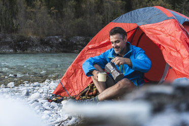 Mature man camping at riverside, espresso maker and cup - UUF16326