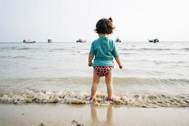 Thailand, Koh Lanta, back view of baby girl wearing UV protection shirt standing at seashore - GEMF02648