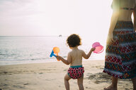 Thailand, Koh Lanta, back view of baby girl with toys on the beach by sunset - GEMF02654