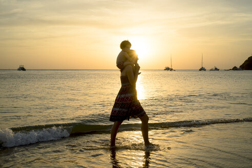 Thailand, Koh Lanta, silhouette of mother with baby girl on her shoulders at seashore during sunset - GEMF02657