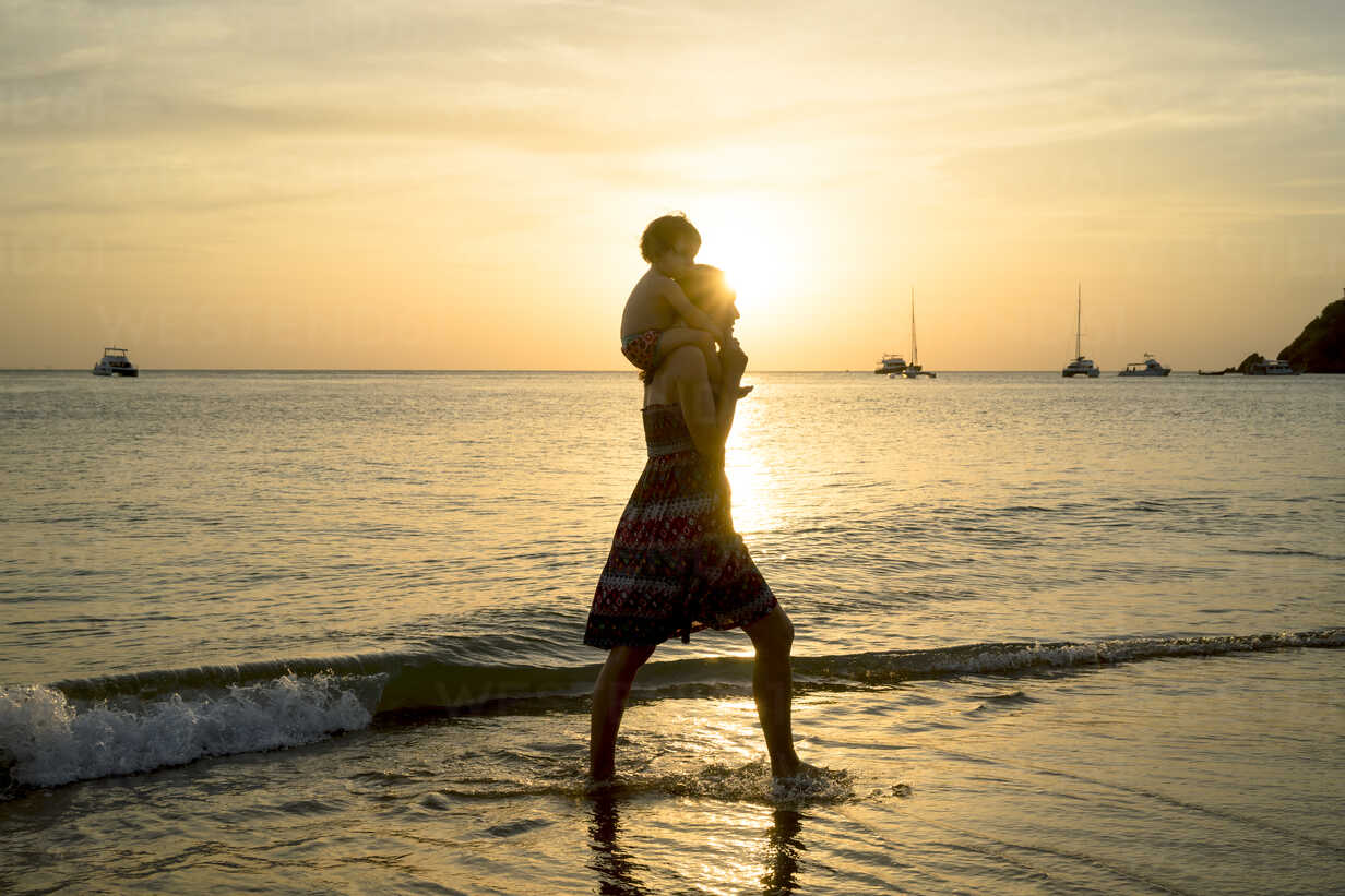 Thailand, Koh Lanta, silhouette of mother with baby girl on her shoulders at seashore during sunset - GEMF02657 - Gemma Ferrando/Westend61