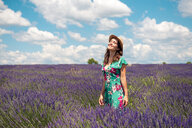 France, Provence, Valensole plateau, happy woman with straw hat standning in lavender field - GEMF02661