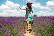 France, Provence, Valensole plateau, back view of woman running among lavender fields in summer - GEMF02667