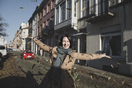 Belgium, Brussels, portrait of happy woman throwing autumn leaves in the air - KMKF00677
