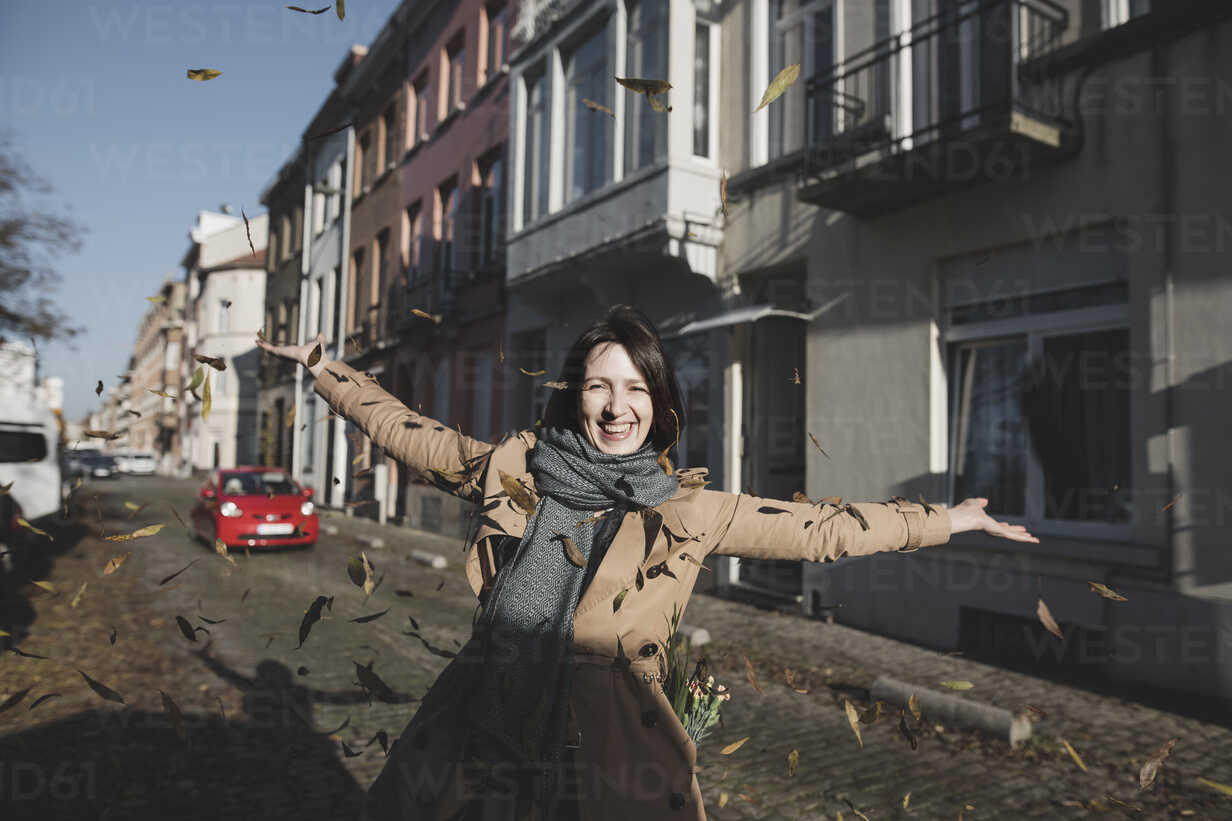 Belgium, Brussels, portrait of happy woman throwing autumn leaves in the air - KMKF00677 - Katharina Mikhrin/Westend61