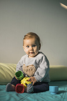 Portrait of baby girl sitting on bed playing with plastic toy - MOMF00558