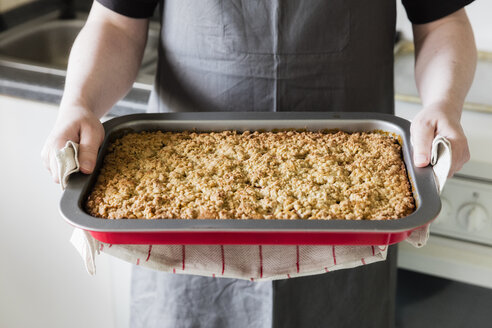 Man in kitchen holding baking tray with homemade rhubarb cake, partial view - EVGF03399
