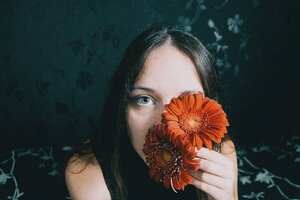 Portrait of a young woman holding flowers over her face - INGF09975