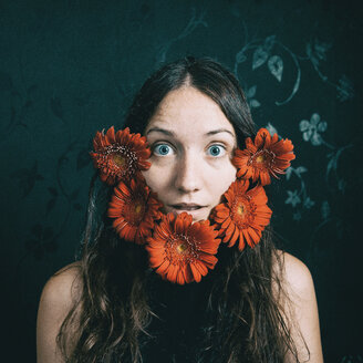 Portrait of a woman looking into the camera with red flowers around her face - INGF09978