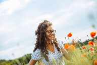 A pretty young woman picking a poppy flower - INGF09984
