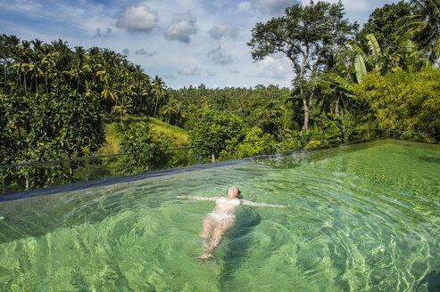 Indonesia, Bali, Ubud, Kamandalu Ubud resort, Woman enjoying the beauftiful overflowing pool - RUNF00384
