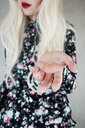 Midsection of a woman with blonde hair holding out her hand - INGF10065