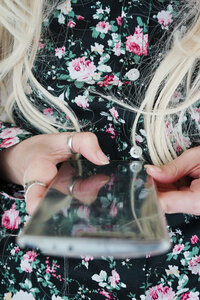 Midsection of a woman wearing floral print holding her phone - INGF10068