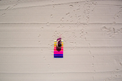 High angle view of a woman sunbathing on a multicolored towel - INGF10197