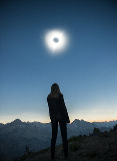 Rear view of woman standing on field at Sawtooth Range during solar eclipse against sky - CAVF59849