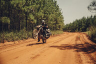 Biker doing stunts while riding motorcycle on dirt road amidst trees - CAVF59861