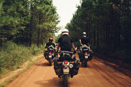 Rear view of bikers riding motorcycles on dirt road by trees - CAVF59864