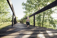 Rear view of shirtless baby boy walking on footbridge by trees against sky - CAVF59900