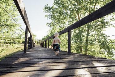 Rear view of shirtless baby boy walking on footbridge by trees against sky - CAVF59900