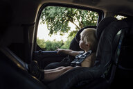 Shirtless baby boy looking through window while sitting in car seat - CAVF59903