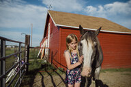 Girl stroking horse while standing at barn against sky - CAVF59906