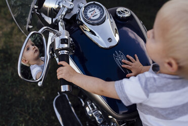 High angle view of baby boy looking away while sitting on motorcycle - CAVF59909