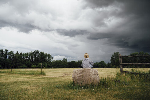 Rear view of girl sitting on rock amidst grassy field against cloudy sky - CAVF59921