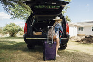 Side view of girl with backpack standing by car trunk - CAVF59924