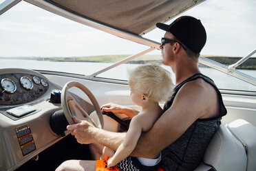 Side view of father with son driving motorboat - CAVF59933