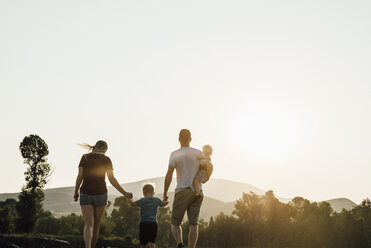 Family walking on field against clear sky during sunset - CAVF59942