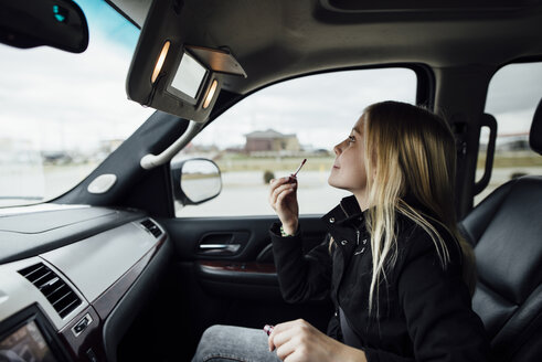 Side view of girl applying lipstick while sitting in car - CAVF59960