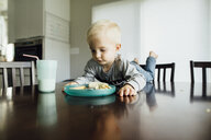 Baby boy eating food while lying on table at home - CAVF59969