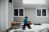 Portrait of girl in warm clothing sitting with Halloween pumpkin on snow by house at backyard - CAVF59972