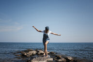 Woman with arms outstretched walking on rocks against sea and sky - CAVF60002