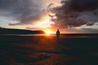 Silhouette of a man standing on the beach during a beautiful sunset - INGF10384