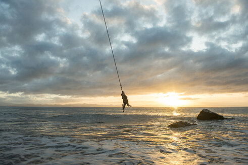 Silhouette man hanging on rope over sea against cloudy sky during sunset - CAVF60022