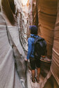 Rear view of female hiker with backpack standing amidst narrow canyons - CAVF60145