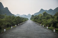 Scenic view of road leading towards mountain against clear sky - CAVF60196